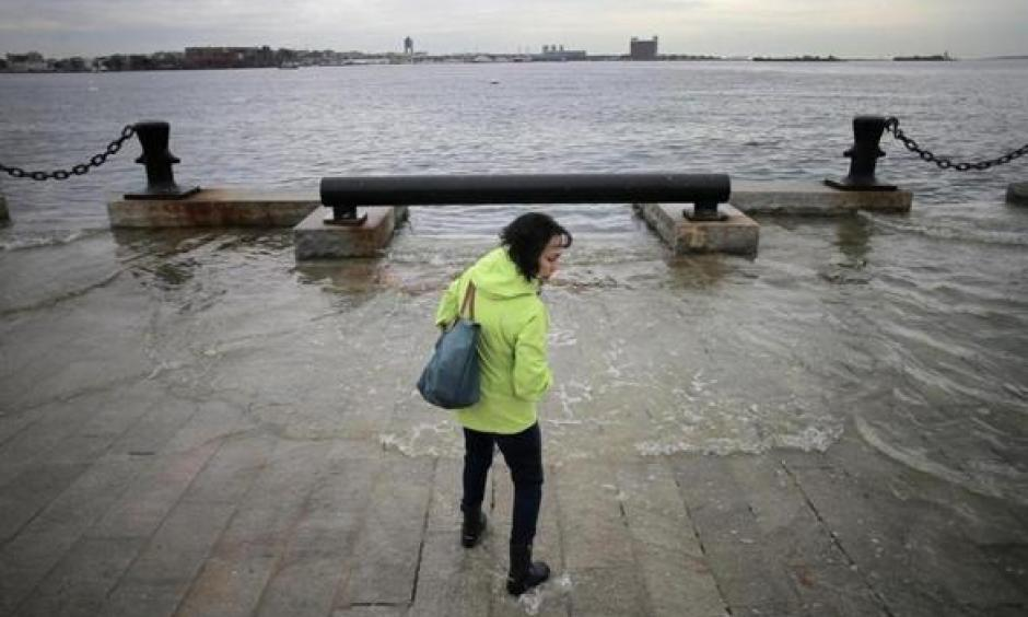 Lynda DeBiccari waded in as the water rose during a King tide at the end of Long Wharf. Photo: Lane Turner