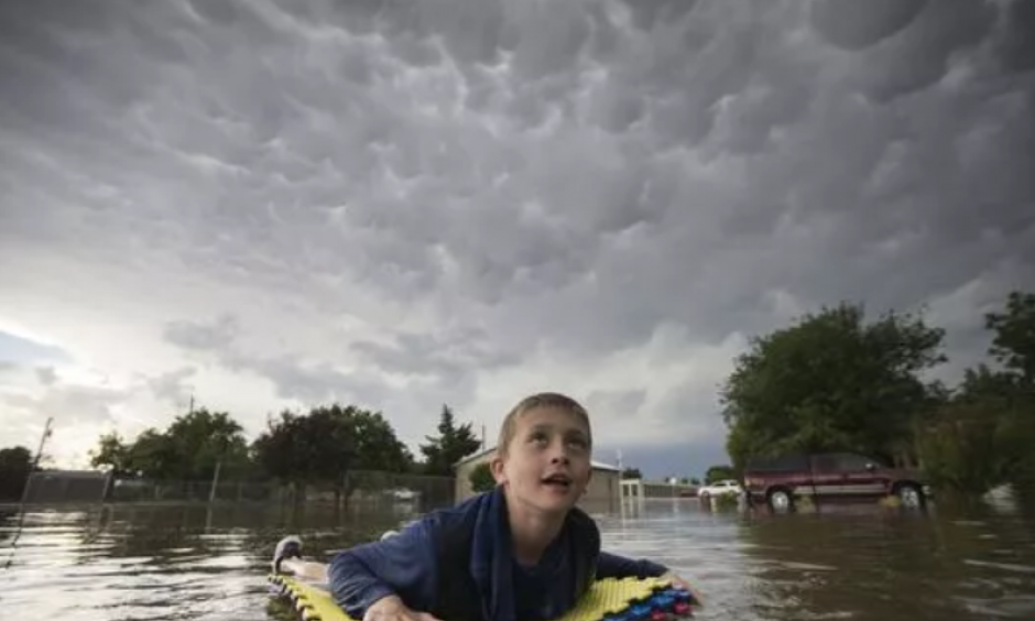 Kevin Weibe floats down his street in Scott City, Kan., while looking up at mammatus clouds after heavy rains inundated the small, western Kansas town on Tuesday, June 19, 2018. High heat will be the main weather story in the central U.S. over the next few days. Credit: Travis Heying, AP