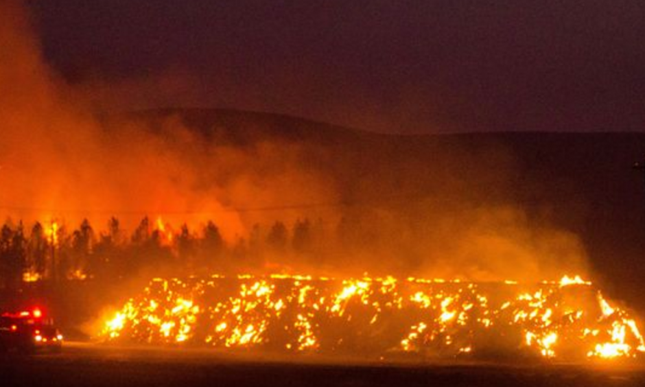 A firetruck moves along Highway 125 past a blazing stack of hay bales north of Walla Walla, Wash., during a large wildfire on Aug. 21, 2016. Photo: Greg Lehman, Walla Walla Union-Bulletin, via AP