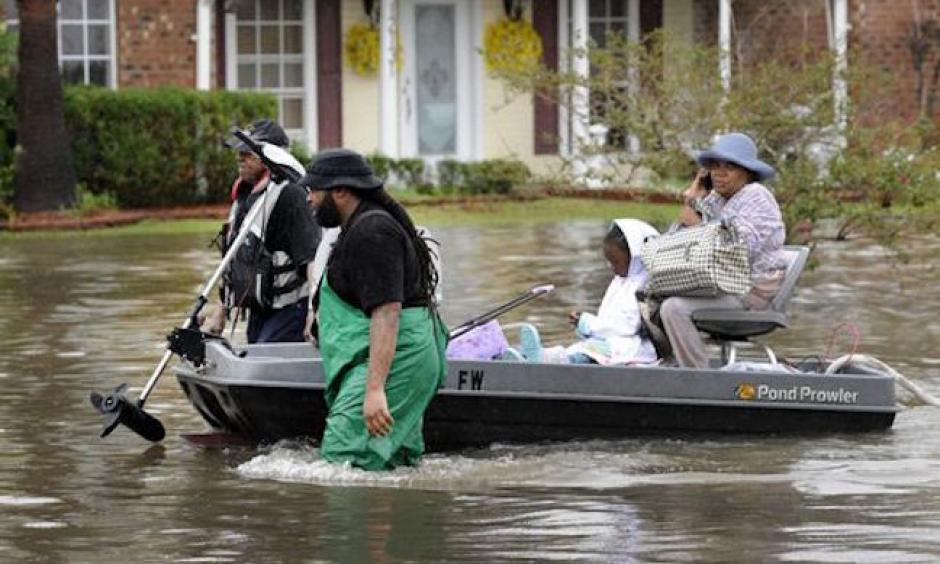 olunteers pull a boat with a woman and young child as they evacuate from their homes on Aug. 13, 2016, in Baton Rouge. Photo: John Oubre/The Advocate via AP