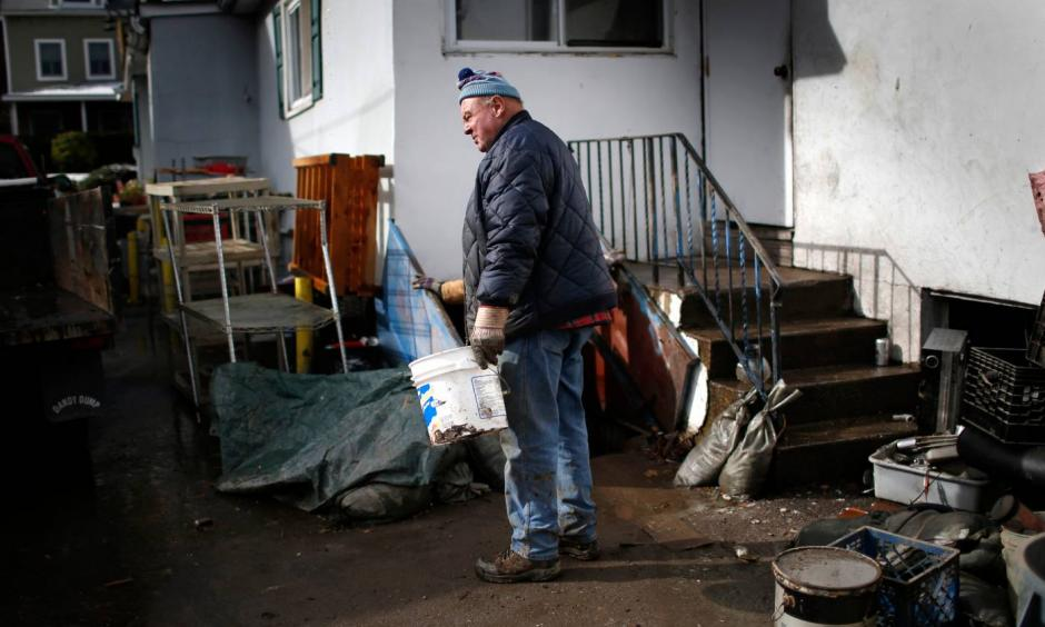 A man takes a break from cleaning out his home flooded by Superstorm Sandy in the Hudson River town of Piermont, New York, November 8, 2012. Photo: Mike Segar, Reuters