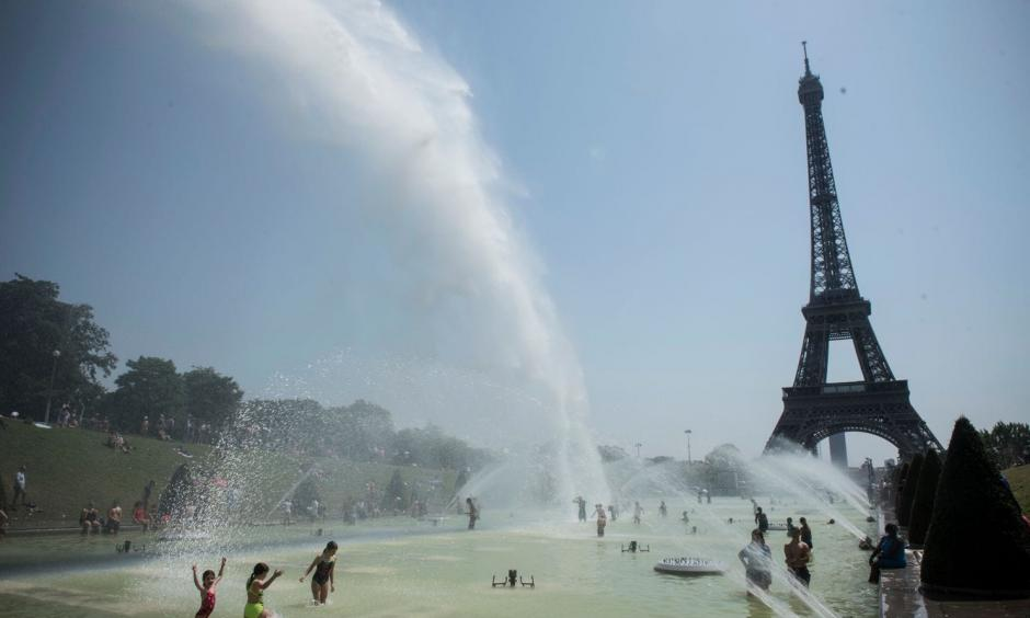 Cooling down at the fountains of Trocadero, near the Eiffel Tower, on a day of record heat in Paris on July 25. Photo: Julien De Rosa, EPA-EFE/Shutterstock