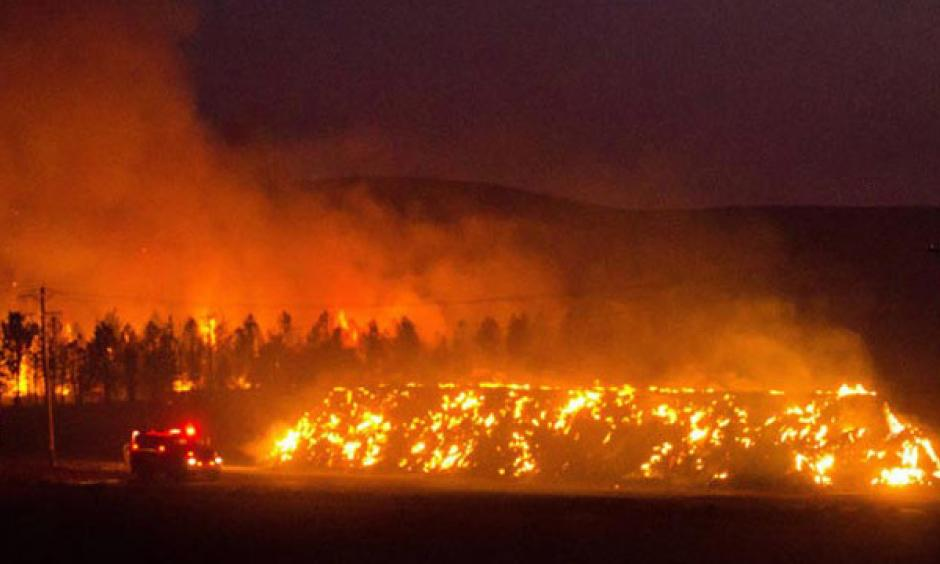 A fire truck moves along Hwy 125 past a blazing stack of hay bales north of Walla Walla during a large wildfire Aug. 21, 2016. The fire, whose cause is under investigation, burned about 15,000 acres. Photo: Greg Lehman / Walla Walla Union-Bulletin via AP