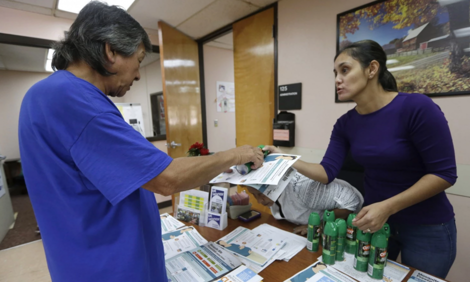 A worker at the Wynwood Community Service Center, right, hands a brochure and a can of insect repellent to a local resident in Miami-Dade County. Photo: Alan Diaz / AP