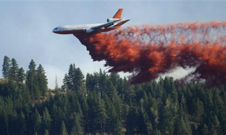 A DC-10 tanker airplane drops fire retardant on a wildfire north of Twisp, Wash. Friday, Aug. 21, 2015. (AP Photo/Ted S. Warren)