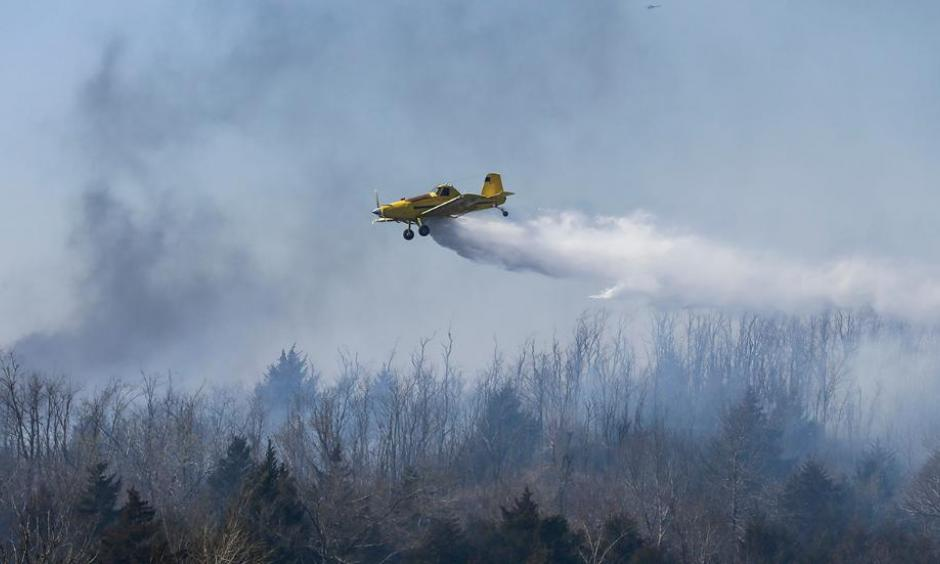 A crop duster drops water on a wildfire north of Hutchinson, Kan., on Tuesday, March, 7, 2017. Wildfires have erupted across the Kansas over the last 24 hours. Photo: Travis Heying, Wichita Eagle via AP