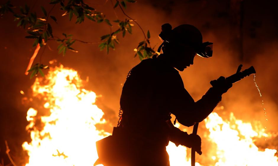 Cal Fire firefighter Trevor Smith battles the Tubbs Fire near Calistoga, Calif., on Thursday. Wildfires in Northern California have killed dozens of people and destroyed thousands of homes and businesses. Credit: Justin Sullivan, Getty Images