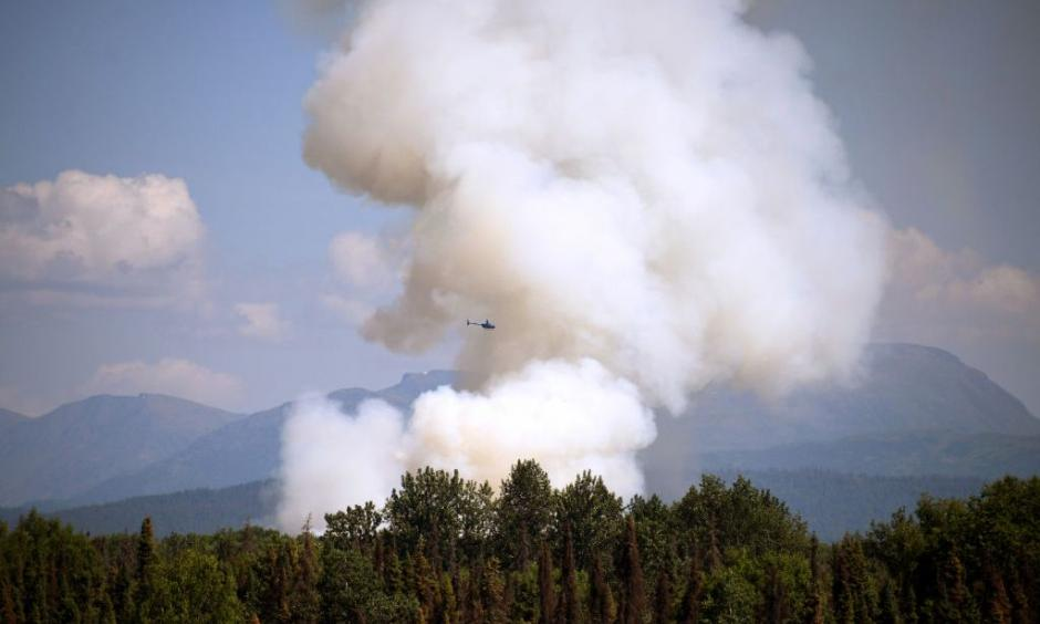 A helicopter passes by as smoke rises from a wildfire on July 3, 2019 south of Talkeetna, Alaska near the George Parks Highway. Credit: Lance King, Getty