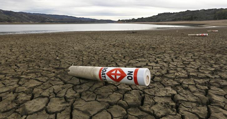 In this Feb. 4 2014 file photo, a warning buoy sits on the dry, cracked bed of Lake Mendocino near Ukiah, California. Photo: Rich Pedroncelli, AP