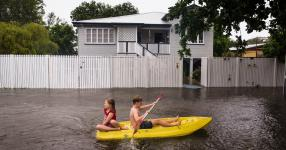 "Residents paddling down a street in Townsville, Australia, on Saturday. ""In seven days, we've received our annual total rainfall,"" the mayor said. Photo: Andrew Rankin, EPA, via Shutterstock"
