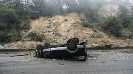 An overturned vehicle blocks a south bound lane next to a mudslide on Highway 17, Tuesday, February 7, 2017. Photo: Marcio Jose Sanchez, AP
