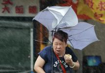 A woman eats and struggles with her umbrella against powerful gusts of wind generated by typhoon Megi across the the island in Taipei, Taiwan, Tuesday, Sept. 27, 2016. Schools and offices have been closed on Taiwan and people in dangerous areas have been evacuated as a large typhoon with 162 kilometers- (100 miles-) per-hour winds approaches the island. Photo: Chiang Ying-ying, Associated Press