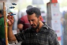 An Iraqi man using an atomizer made available for people outside a shop selling cooling and ventilation products on July 20, the first day of a two-day holiday for government employees Iraqi authorities announced due to the heat. Photo: Ahmad Al-Rubay, Agence France-Presse