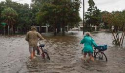 A couple walks their bikes through a flooded street in Mandeville, Louisiana, north of New Orleans, on Sunday, July 14, 2019, after Tropical Storm Barry came ashore. Credit: Seth Herald, AFP, Getty Images