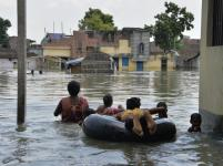 Indian residents wade through flood waters in Malda in the Indian state of West Bengal. Photo: AFP