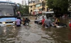 Commuters make their way through a flooded street following heavy rains in Mumbai, India, Aug. 29, 2017. Photo: Rajanish Kakade, AP