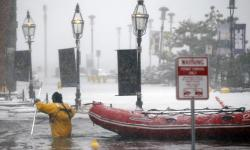 A firefighter wades through waters from Boston Harbor, which flooded on to Long Wharf on 4 January 2018. Photo: Michael Dwyer, AP