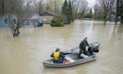 Two men move along a flooded street using a small boat in the town of Rigaud, west of Montreal, Sunday, following flooding in the region. In total, nearly 1,900 homes are flooded in 126 municipalities in Quebec. Photo: Graham Hughes, The Canadian Press