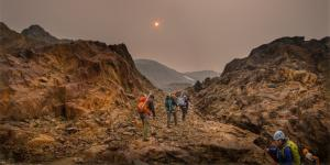 Haze from wildfire smoke obscures the sun as U of A researcher Zac Robinson leads students on a hike in B.C.'s Monashee Mountains in August 2018. Robinson is one of the editors of a new report focusing on how wildfires are affecting Canada's alpine regions. Photo: Mary Sanseverino