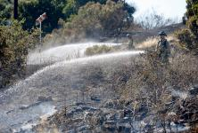 Firefighters extinguish hotspots from a four-alarm fire that consumed 24 acres on a dry hillside in Cordelia, Calif. on Friday, June 7, 2019. Photo: Paul Chinn, San Francisco Chronicle