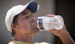 Delfino Villagomez drinks water while laying asphalt on Thursday, July 20, 2017, in Omaha, Neb. Temperatures hit 98°F in Omaha on Thursday after a morning low of 80°F. Photo: Kent Sievers, Omaha World-Herald via AP