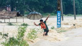 A Nepalese man looses his balance while crossing a flooded street in Birgunj, Nepal, Sunday, Aug. 13, 2017. An official said torrential rain, landslides and flooding have killed dozens of people in Nepal over the past three days, washing away hundreds of homes and damaging roads and bridges across the Himalayan country. Photo: Manish Paudel, AP